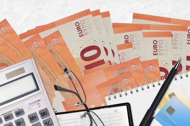 Notas de 10 euros e calculadora com óculos e caneta