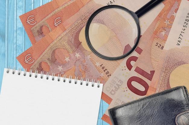 Notas de 10 euros e lupa com bolsa preta e bloco de notas