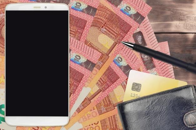 Notas de 10 euros e smartphone com bolsa e cartão de crédito