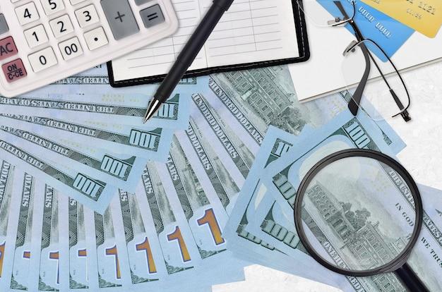 Notas de 100 dólares americanos e calculadora com óculos e caneta. conceito de temporada de pagamento de impostos ou soluções de investimento. procurando um emprego com alto salário