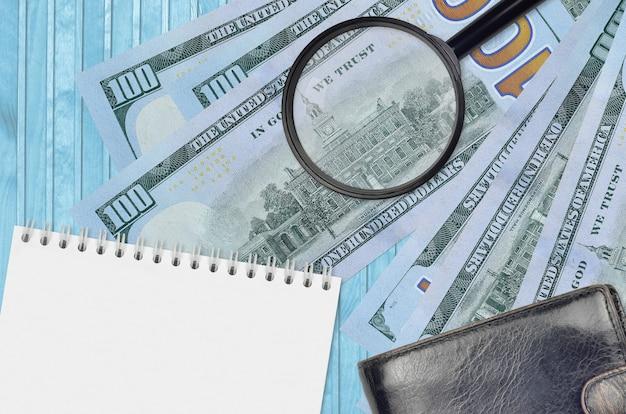 Notas de 100 dólares americanos e lupa com bolsa preta e notep