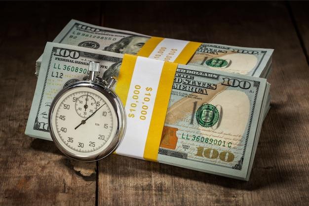 Notas de 100 dólares com relógio retrô