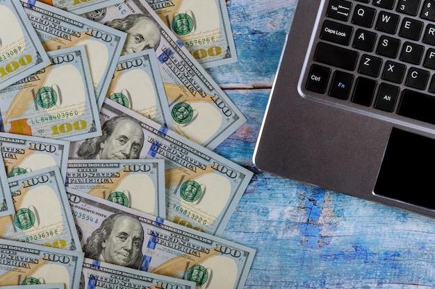 Notas de 100 dólares de papel-moeda no conceito financeiro de teclado de laptop