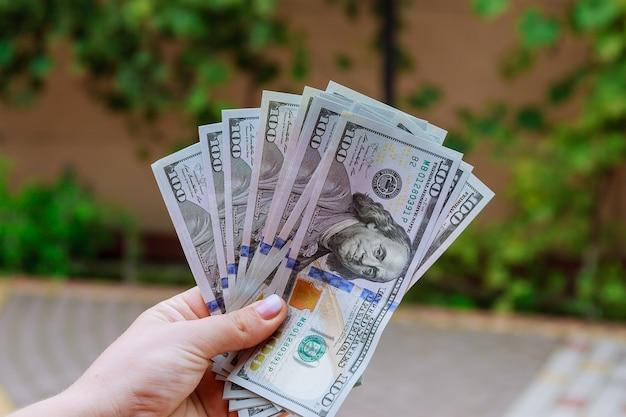 Notas de 100 dólares nas mãos de uma mulher. conte ou gaste dinheiro.