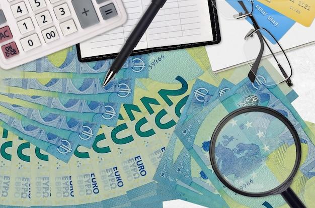 Notas de 20 euros e calculadora com óculos e caneta