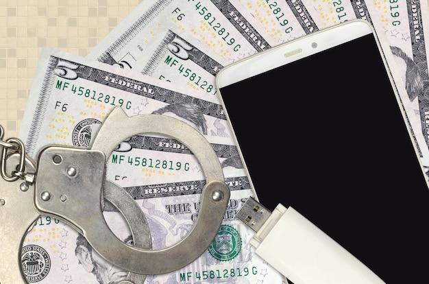 Notas de 5 dólares e smartphone com algemas policiais