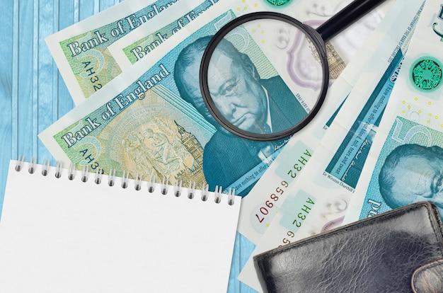 Notas de 5 libras esterlinas e lupa com bolsa preta e bloco de notas