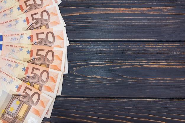 Notas de 50 euros em fundo de madeira com espaço de cópia.