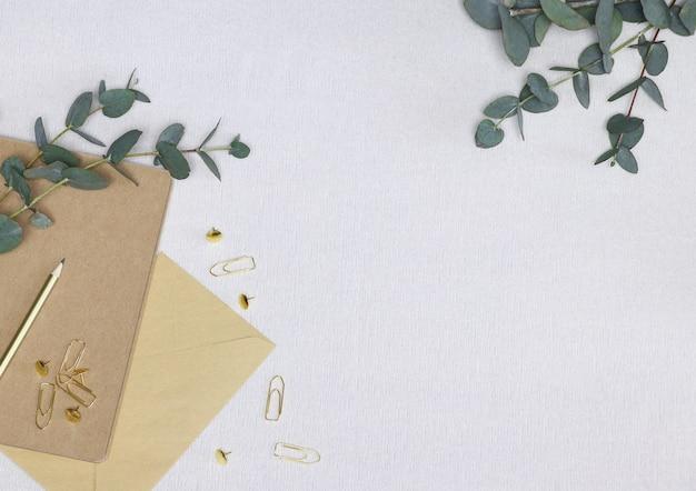 Notas de artesanato com lápis de ouro, clipes de papel, envelope e galhos de eucalipto verdes