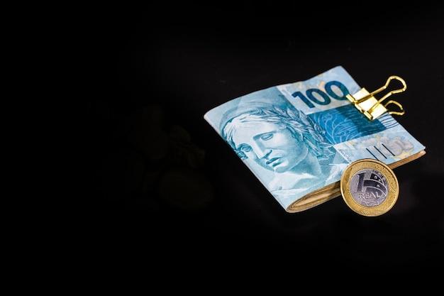 Notas de banco de cem reais e moeda de um real, dinheiro brasileiro