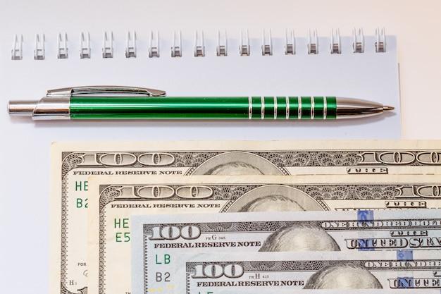 Notas de cem dólares americanos. uma caneta esferográfica e um caderno ao lado das notas. negócios e finanças. dinheiro. fundo branco.