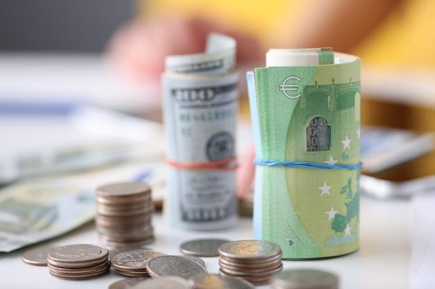 Notas de cem dólares e cem euros com moedas estão na mesa de investimento lucrativo
