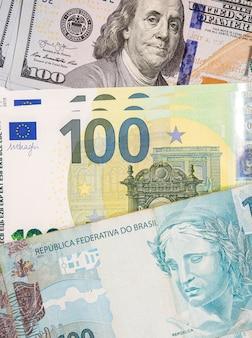 Notas de cem dólares, euros e reais