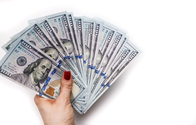 Notas de cem dólares na mão de uma mulher em um fundo branco. espaço para texto