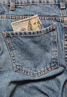 Notas de cem dólares no bolso de trás do jeans amarrotado