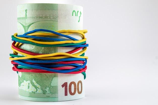 Notas de cem euros em dinheiro com cordas de borracha coloridas ao redor