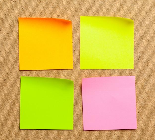 Notas de cor autocolante sobre fundo de placa de cortiça