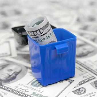 Notas de dinheiro americanas são jogadas na lixeira em uma infinidade de notas de cem dólares