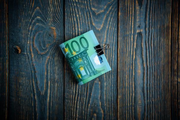 Notas de dinheiro do euro em um fundo escuro de madeira.