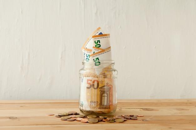 Notas de dinheiro do euro no frasco de vidro na mesa de madeira com moedas de euro ou centavos. conceito de negócios. poupança de dinheiro em pote de vidro em casa.