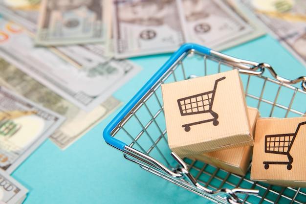 Notas de dinheiro, dólar e cesta de compras com caixas em azul