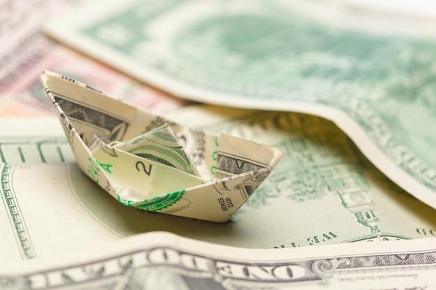 Notas de dinheiro e barcos de papel.