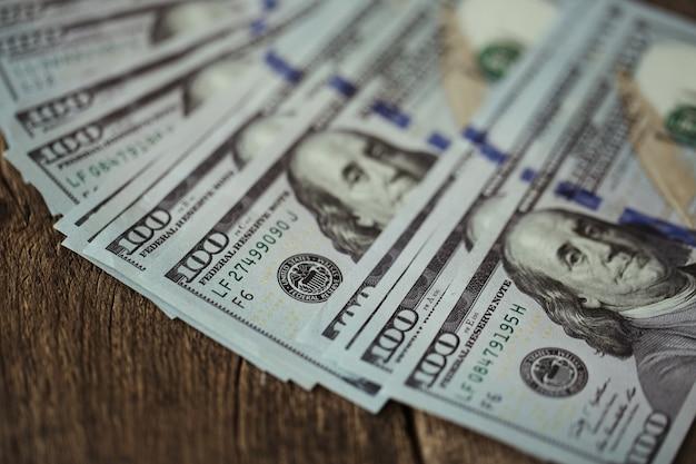 Notas de dinheiro em dólares americanos espalhadas na velha mesa de madeira