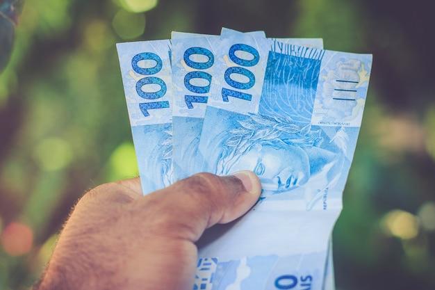 Notas de dinheiro (reais) na mão. desfoque de fundo.