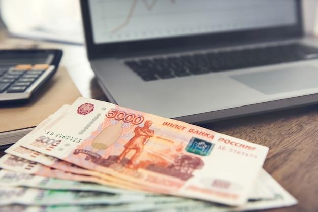 Notas de dinheiro rublo russo em uma mesa de madeira com um laptop e uma calculadora