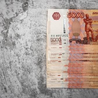 Notas de dinheiro russas de cinco mil rublos, o pacote está pendurado em uma superfície cinza