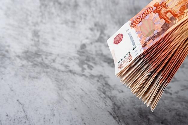 Notas de dinheiro russo de cinco mil rublos, o pacote paira sobre um fundo cinza.