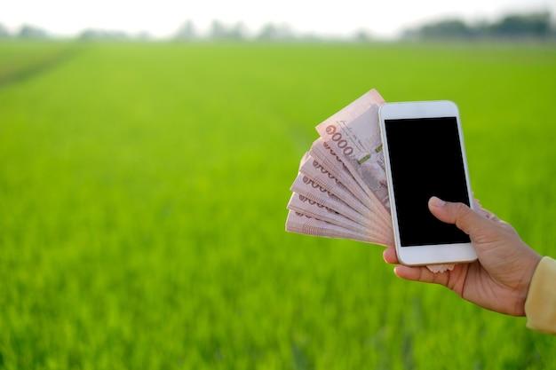 Notas de dinheiro tailandês mil baht e smartphone