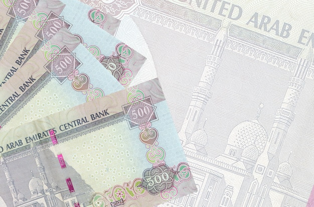 Notas de dirhams dos emirados árabes unidos empilhadas no fundo de uma grande nota semitransparente