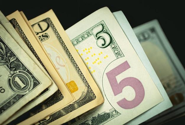 Notas de dólar americano em ambiente escuro na foto em close