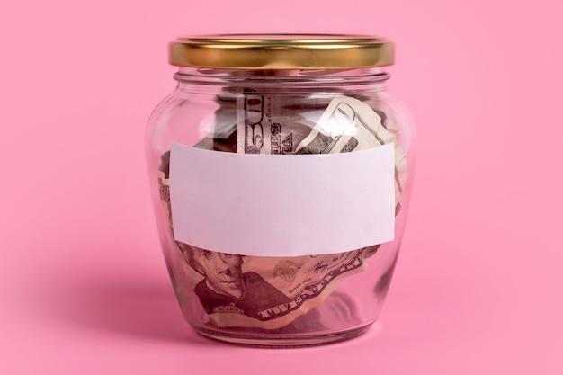 Notas de dólar americano em um frasco de vidro com rótulo em branco sobre fundo rosa