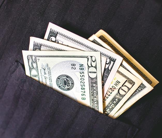 Notas de dólar americano no bolso de uma camisa preta
