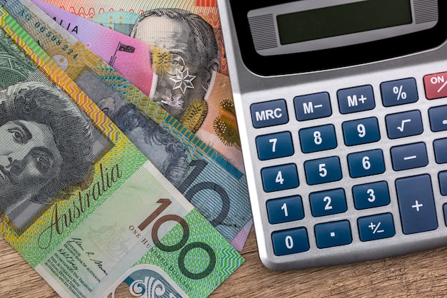 Notas de dólar australiano com calculadora na mesa de madeira