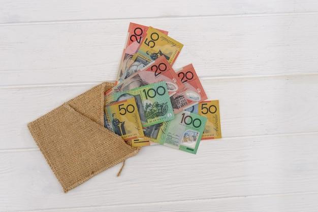 Notas de dólar australiano com envelope de material em fundo claro