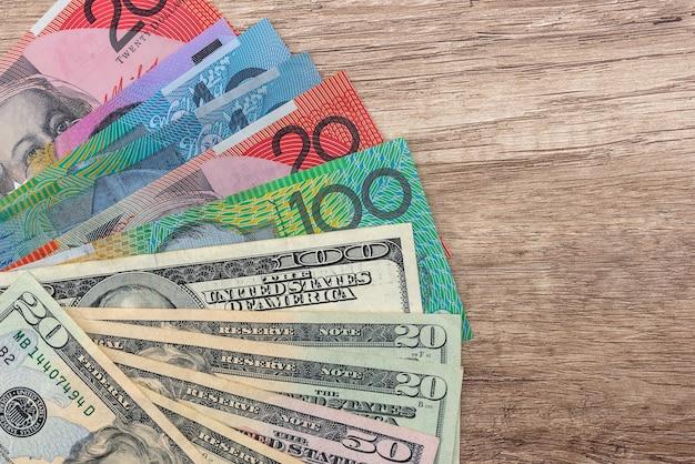 Notas de dólar australiano e americano na mesa de madeira