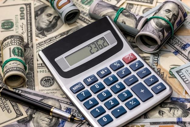 Notas de dólar, caneta e calculadora