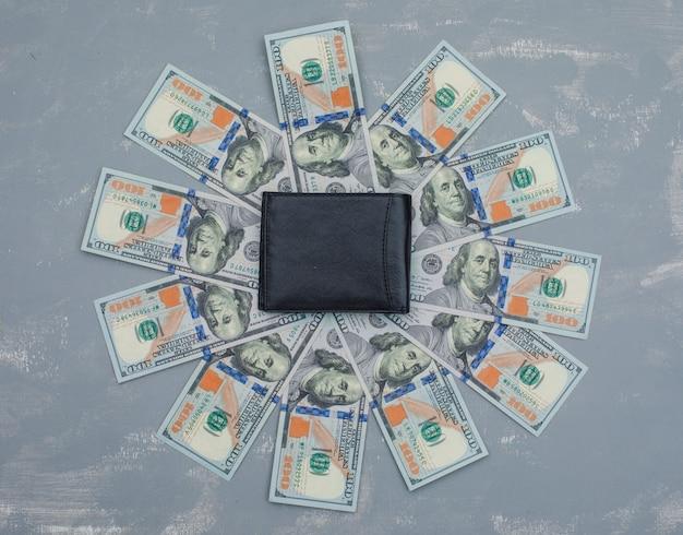 Notas de dólar, carteira na mesa de gesso.