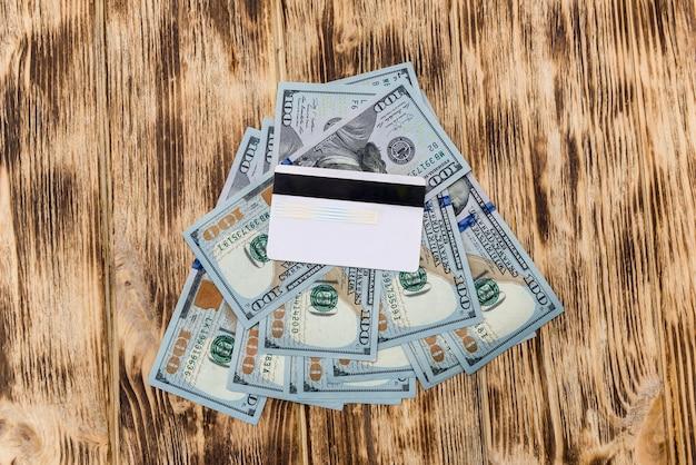 Notas de dólar com cartão de crédito na mesa de madeira Foto Premium