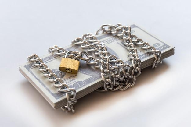 Notas de dólar com corrente e cadeado, dinheiro de segurança e conceito de investimento.