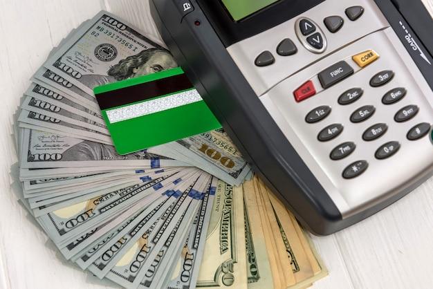 Notas de dólar com terminal e cartão de crédito