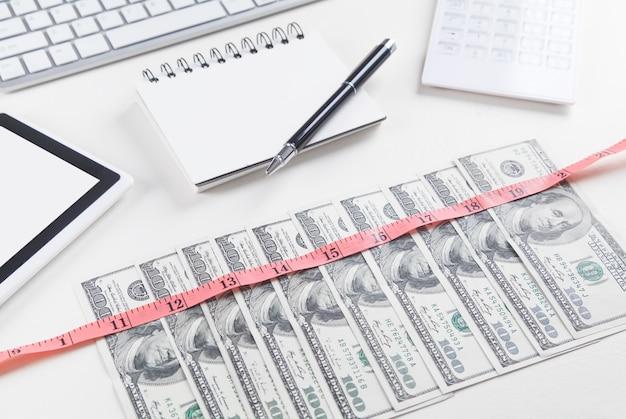 Notas de dólar com uma fita métrica bloco de notas caneta calculadora tablet