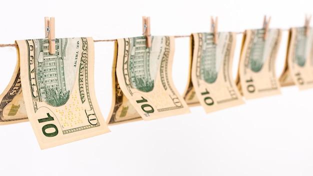 Notas de dólar de vista lateral pendurado no varal