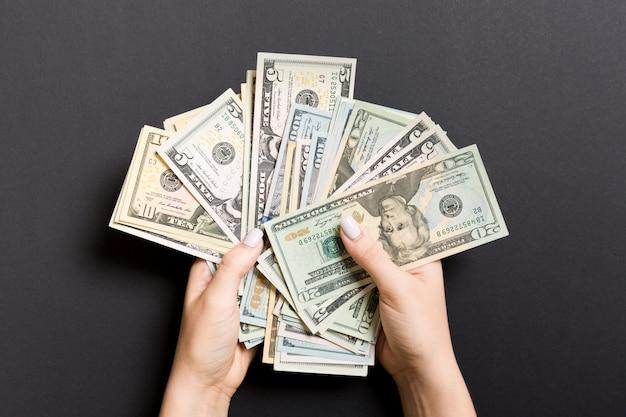 Notas de dólar diferentes nas mãos femininas