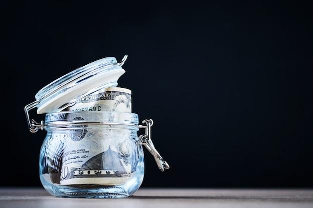 Notas de dólar dos eu em um frasco de vidro com espaço da cópia. poupar dinheiro e investimento conceito
