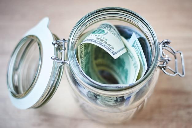 Notas de dólar dos eua em um frasco de vidro na madeira