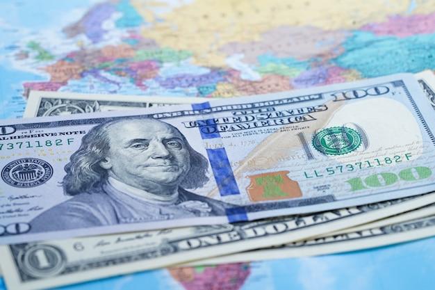 Notas de dólar dos eua no fundo de mapa do mundo globo.
